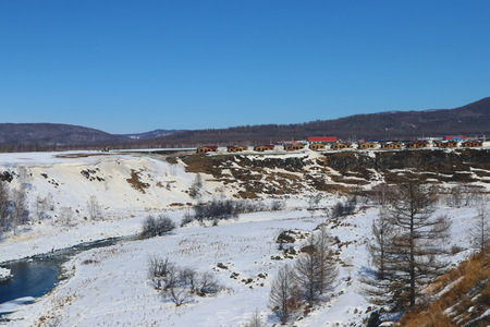 A small village on the side of the frozen mountain in the Aershan Forest Park