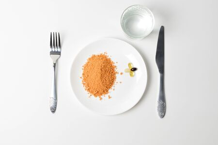 Tomato protein soup powder and multivitamins on a plate. Meal replacement. Dry soup. Multivitamins, astaxanthin, fish oil, omega pills.
