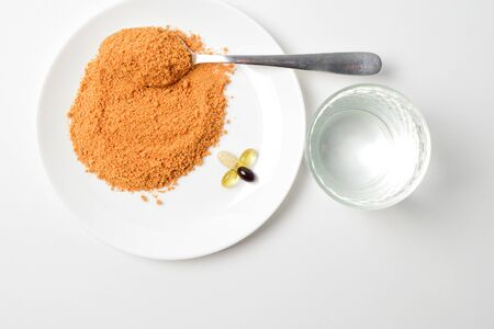Tomato protein soup powder on a spoon. Meal replacement. Dry soup. Multivitamins, astaxanthin, fish oil, omega pills on a plate.  Closeup.