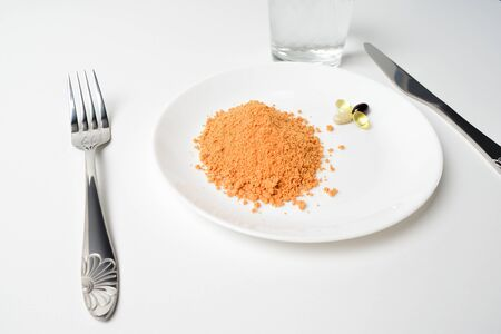 Meal replacement. Dry soup.  Tomato protein soup powder and multivitamins on a plate. Multivitamins, astaxanthin, fish oil, omega pills.