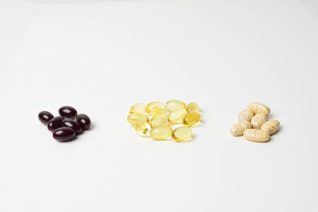 Three bunches of multivitamins, fish oil and astaxanthin. Polyunsaturated fatty acids in the middle. White background. Close-up.