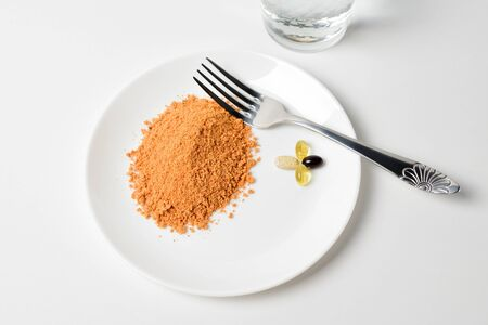 Protein soup powder on a plate. Meal replacement. Dry soup. Multivitamins, astaxanthin, fish oil, omega pills. Closeup. Banco de Imagens