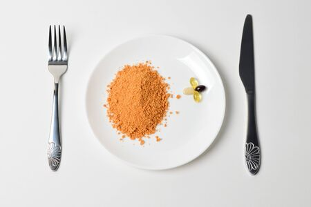 Meal replacement. Protein powder on a plate. Dry soup. Multivitamins, astaxanthin, fish oil, omega pills.