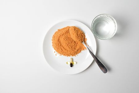 Tomato protein soup powder on a spoon. Glass of water. Meal replacement. Dry soup. Multivitamins, astaxanthin, fish oil, omega pills.