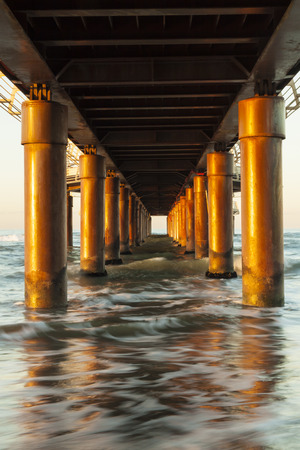architectonics: view a seascape from under a pier marin pillars lit by the morning sun