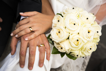 wife of bath: Close-up view of a bridal bouquet made of pale yellow roses and hands of the couple in the background
