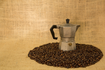 expressed: View of a coffee maker on a sea of ??coffee beans and jute in the background