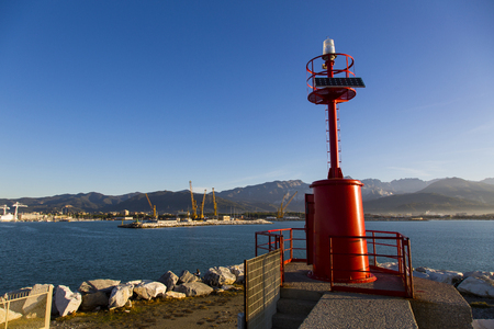 costal: Costal landscape with lighthouse in the foreground, the commercial port and the mountain range in the background Stock Photo
