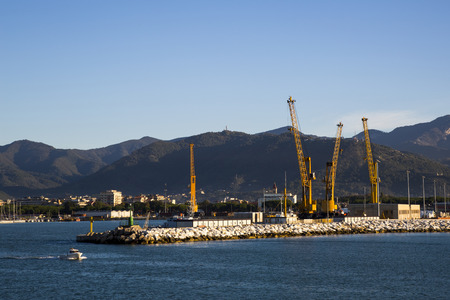 shipload: Panoramic view of a commercial port in a sunny morning with mountains in the background