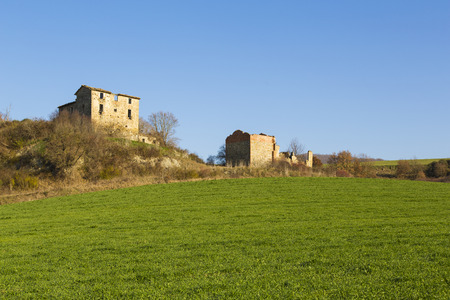 meadowland: Panoramic view of a field for the agriculture with an old farm in the background