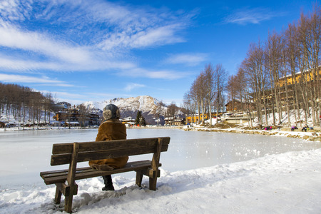 snowy landscape: View from behind of a woman sitting on a bench in a Tuscan snowy landscape