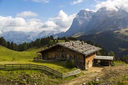 sud tirol: View of a mountain hut on a sunny day with mountains in the background