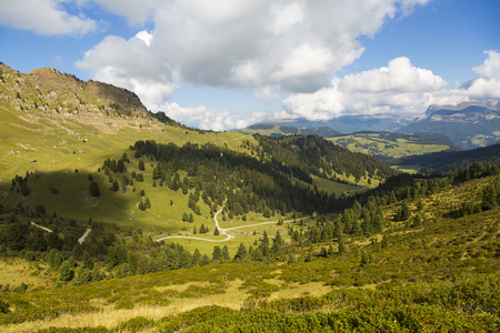 Mountain landscape with valley, trails, green fields and blue sky with clouds Stock Photo