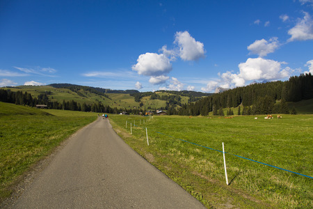Hiking trail between green fields blue sky with clouds Stock Photo