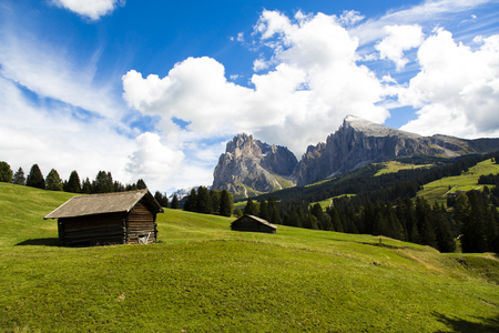 panoramic view of the Seiser Alm in a sunny day with blue sky and clouds with refuge in foreground and mountain range in the background