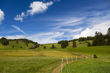 panoramic view of the Seiser Alm in a sunny day with blue sky and clouds with path in the foreground Stock Photo