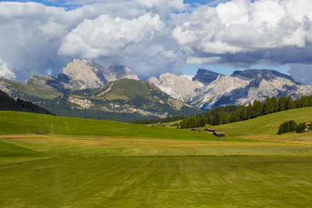 panoramic view of the Seiser Alm in a sunny day with blue sky and clouds with mountain range in the background
