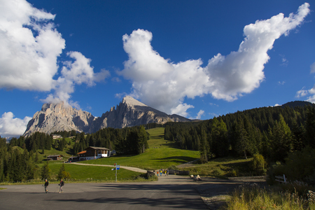 sud tirol: mountain landscape with trees, blue sky, clouds and mountain range on the background Editorial
