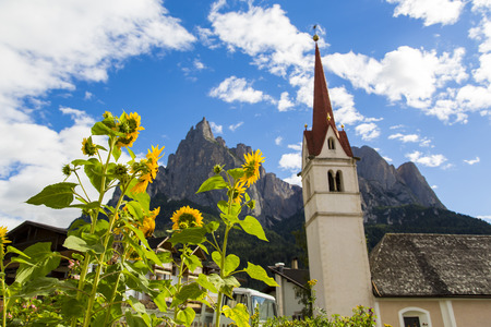 Seiser Alm Schlern, IT- September 19. Botton view of the St. Marys Assumption with sunflowers in the foreground and Seiser Alm on the background