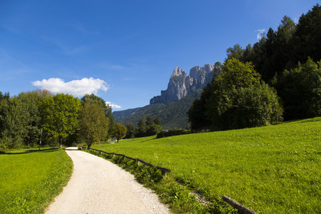 sud tirol: View of a passable trail walk with green fields and mountain range in the background and bllue sky