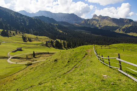 Mountain landscape with wooden fence, shelter and hiking trails