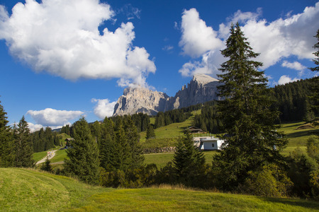 sud tirol: mountain landscape with trees, blue sky, clouds and mountain range on the background Stock Photo