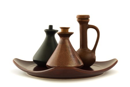 Three massage oil ceramic bottles standing on a brown squaere plate, isolated on white Stock Photo