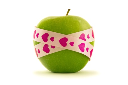 Green apple with pink heart pattern gift ribbon, isolated on white photo