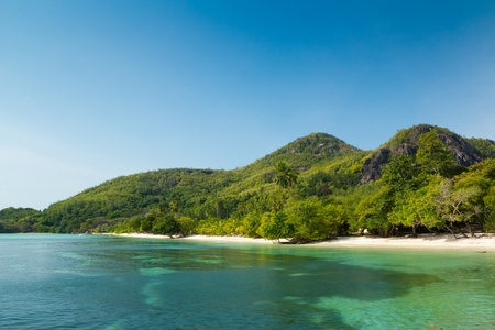 A small turquoise crystal clear tropical beach by mountain in St Anne Island, Seychelles