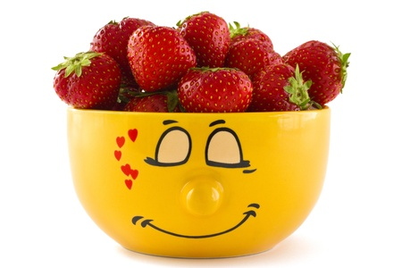 Large yellow cup with a shy face print full of ripe strawberries, isolated on a white background.