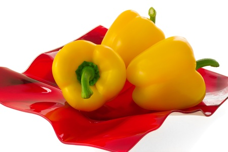 Three yellow bell pepper on a red plate, isolated on white background. Stock Photo - 10171566