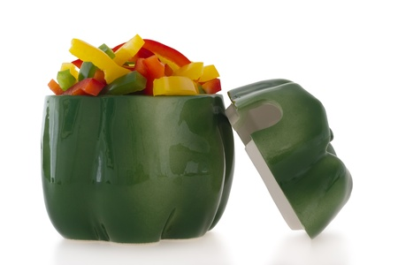 bell shaped: Ceramic green pepper shaped ornament filled with cut colofrul bell pepper slices.