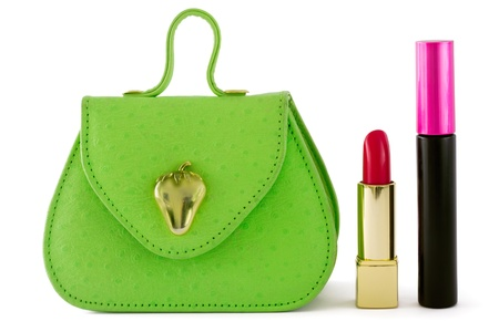 Small green bag with red lipstick and mascara on the side, isolated on white background