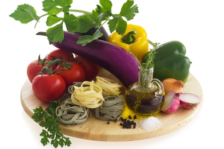 Pasta ingredients (paglia (round pasta), tomato, eggplant, bell pepper, salt, pepper, onion, garlic, olive oil, celery) on wooden board, isolated on white background