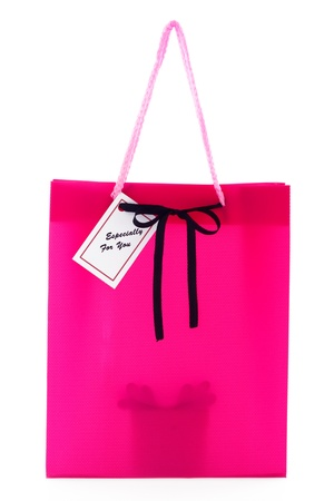 Pink gift bag with small card and a silhouette of a present inside isolated on white background Stock Photo