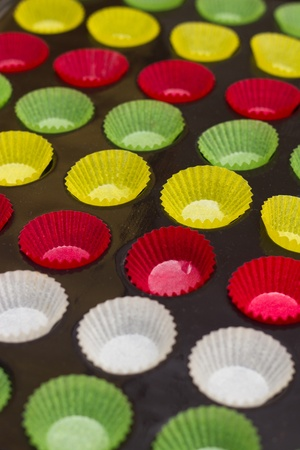 Mini cupcake tin with vibrant colorful cupcake papers ready to be filled with batter photo