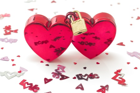 Two red hearts connected with padlock, with small decorations, isolated on white background photo