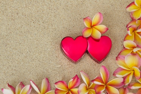 Group of frangipani, plumeria flowers, together with two red hearts, on sand