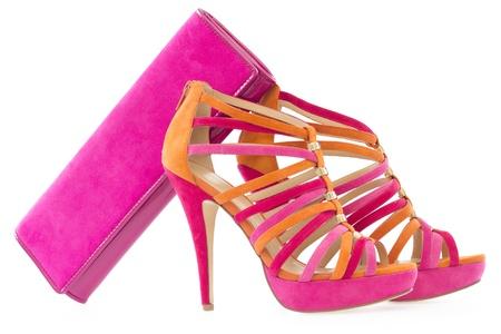 Pare van roze en oranje schoenen en een bijpassende tas, op een witte achtergrond