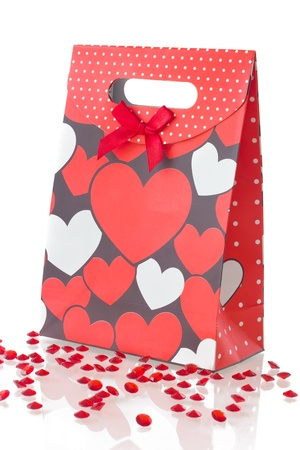 Red gift bad with pattern of hearts, isolated on white background   photo