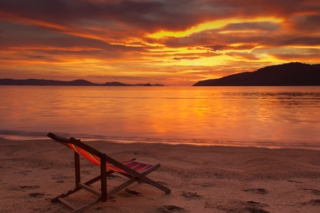 Dramatic sunrise in Phuket, Thailand, with resting chair on foreground Stock Photo - 13680027