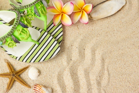 Green Sandals, seashells, starfish and frangipani on sand  photo