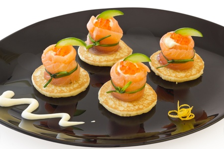 Red salmon roll with cheese, caviar and cucumber on  blini � base, on black plate  photo