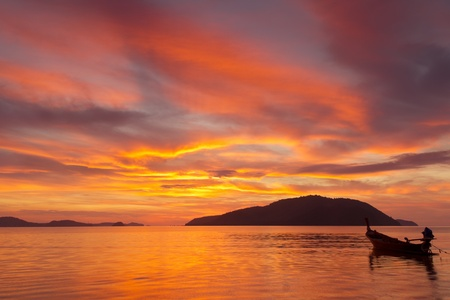 Beautiful Sunrise in Phuket, Thailand, with far island and a fishing boat silhouette