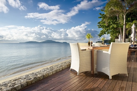 dining table and chairs: White table with chairs on decking, by the beach