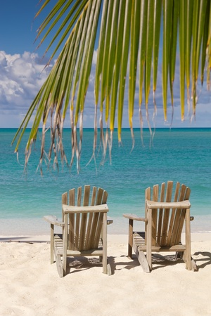 Beach chairs on white sand beach with cloudy blue sky and sun photo