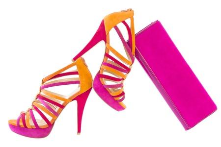 Pare de zapatos de color rosa y naranja y una bolsa a juego, aislado sobre fondo blanco