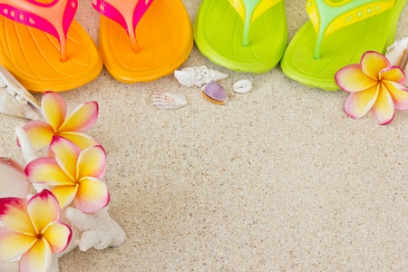 Flip Flops in the sand with shells and frangipani flowers  Summertime on beach concept