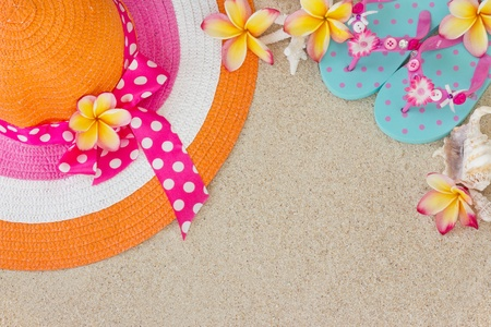 flops: Orange and pink hat and  blue Flip Flops in the sand with shells and frangipani flowers  Summertime on beach concept