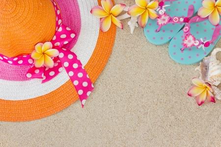 Oranje en roze hoed en blauwe Flip Flops in het zand met schelpen en frangipani bloemen Summertime op het strand concept van